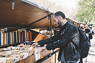 France, Paris, man looking for old books in the Bouquinistes of Paris along the banks of the Seine - GEM000966