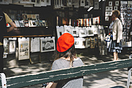 France, Paris, woman wearing a french red beret sitting on a bench in front of old book stores - GEM000969