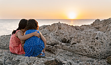 Back view of two little sisters crouching at rocky coast watching sunset - MGOF002252