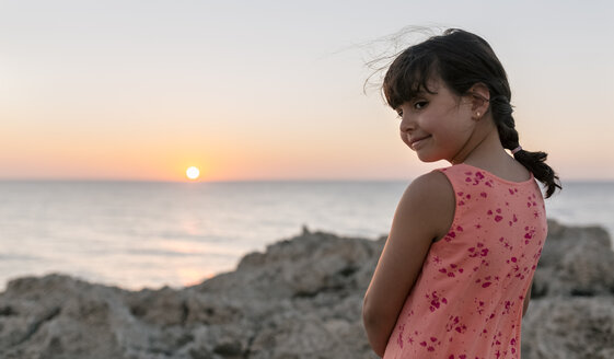 Smiling little gir at rocky coast by sunset - MGOF002255