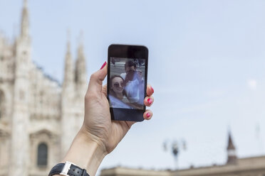 Italy, Milan, tourist taking selfie with smartphone, close-up - JUNF000607