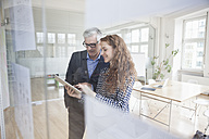 Businessman and woman using digital tablet in office - RBF004990