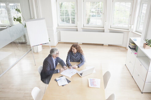 Businessman and woman in boardroom - RBF005011