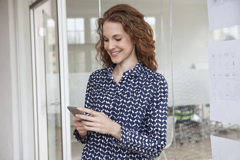 Smiling woman in office looking at cell phone - RBF005026