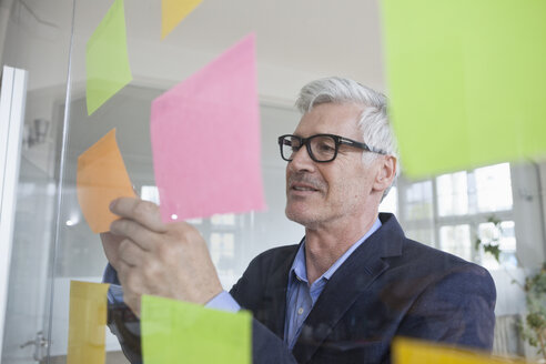 Businessman in office attaching adhesive notes at glass pane - RBF005038