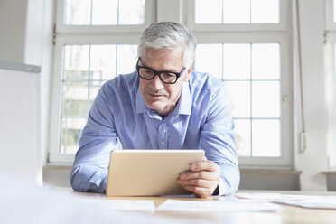 Mature businessman sitting on chair in office holding tablet - RBF005050