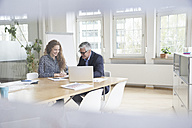 Businessman and woman sitting at boardroom table looking at documents - RBF005062