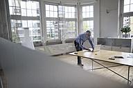 Mature businessman using laptop on boardroom table - RBF005071