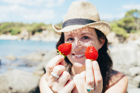 Hands of woman on the beach holding strawberries - GEMF000981