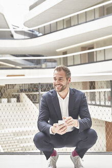 Smiling businessman in office building holding cell phone - FMKF002912