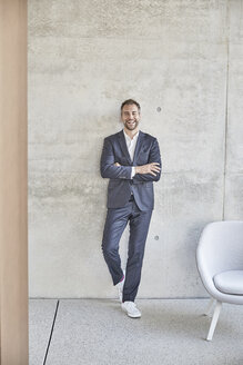 Laughing businesssman standing at concrete wall - FMKF002915