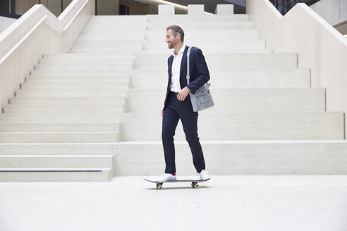 Businesssman riding skateboard at staircase - FMKF002924