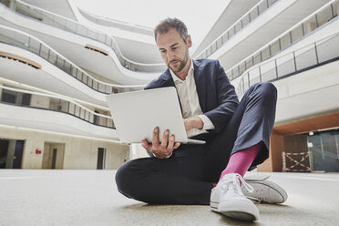 Businesssman sitting on floor in office building using laptop - FMKF002927
