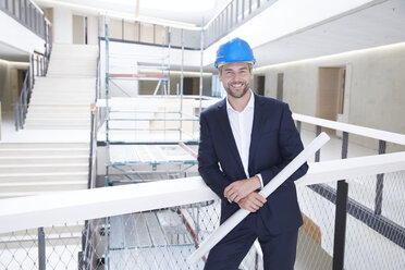 Smiling architect in office building wearing hard hat - FMKF002930