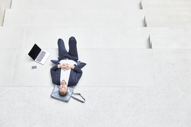 Businesssman lying on stairs next to laptop and cell phone - FMKF002936