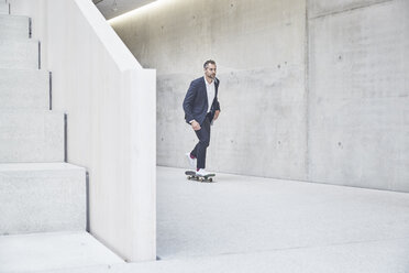 Businesssman riding skateboard along concrete wall - FMKF002945