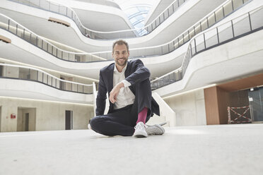 Smiling businessman sitting on the floor in office building - FMKF002951