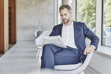 Businesssman sitting on chair reading newspaper - FMKF002954