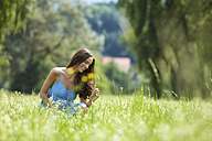 Young woman, blue dress, on meadow, flower - MAEF011936