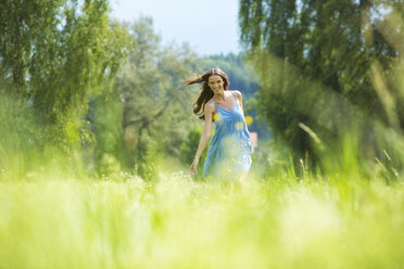 Young woman, blue dress, on meadow - MAEF011939