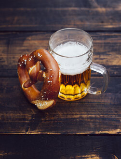 Pretzel and glass of beer on dark wood - PPXF000024