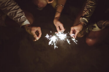 Hands of three friends holding sparklers on the beach at night - DAPF000298