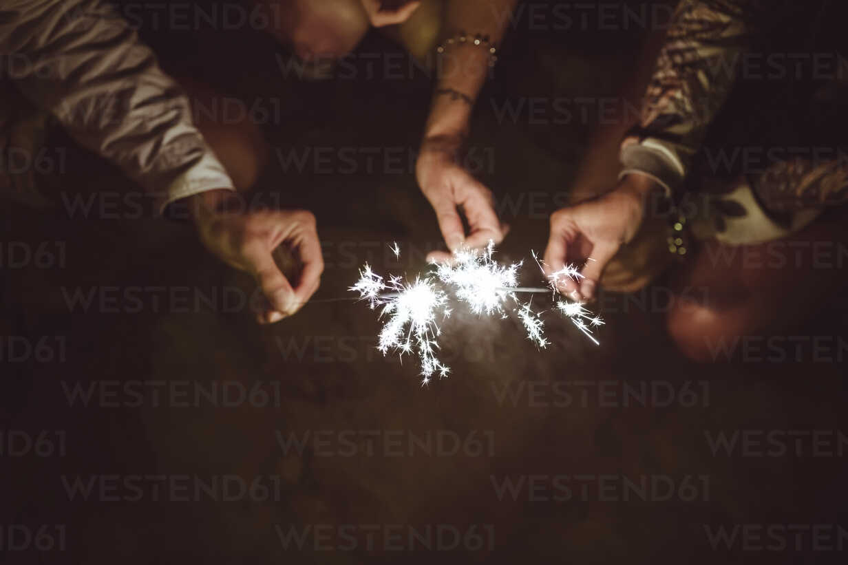 Hands of three friends holding sparklers on the beach at night - DAPF000298 - David Pereiras/Westend61