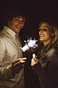 Young couple in love holding sparklers on the beach at night - DAPF000301
