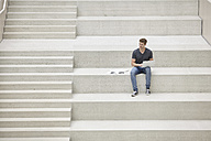 Young man sitting on stairs using laptop - FMKF002975