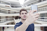 Young man taking a selfie in modern office building - FMKF002981