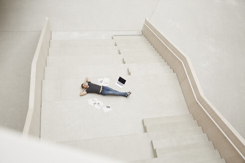 Young man lying on staircase with laptop and papers - FMKF002996