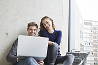 Smiling young couple sitting at concrete wall sharing laptop - FMKF003005