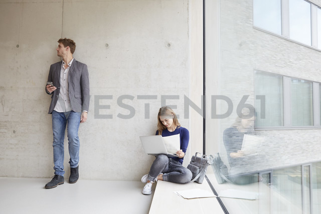 Young woman with papers and laptop and man with cell phone at concrete wall - FMKF003008