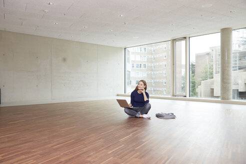 Young woman using laptop in empty room - FMKF003011