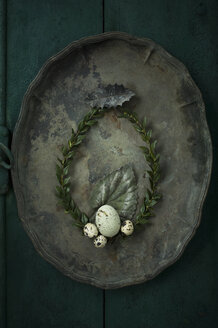 Box tree wreath, goose egg and quail eggs on an old metal tray - ASF005991