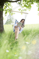 Happy woman relaxing with tablet in a hanging chair under a tree - MAEF011948