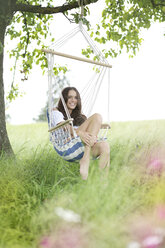 Happy woman relaxing in a hanging chair under a tree - MAEF011951