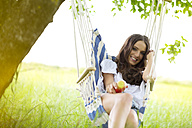 Happy woman with apple relaxing in a hanging chair under a tree - MAEF011954