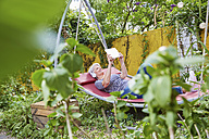 Woman relaxing on a swing in the garden using digital tablet - FMKF003032