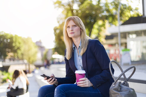Blond businesswoman with coffee to go and smartphone looking at distance - NAF000016