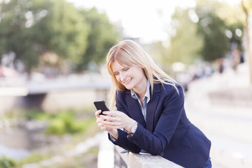 Smiling businesswoman leaning on railing looking at cell phone - NAF000028