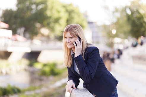 Smiling blond businesswoman on the phone - NAF000031