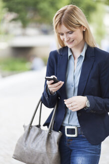 Smiling blond businesswoman looking at smartphone - NAF000034