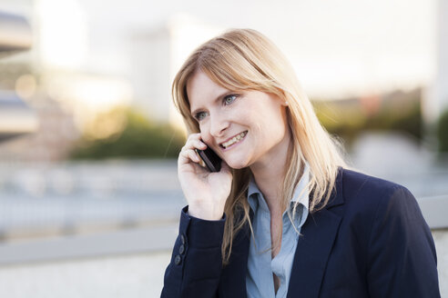 Smiling blond businesswoman on the phone - NAF000037