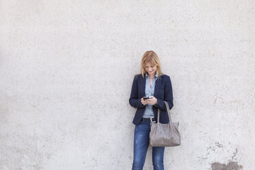 Smiling blond businesswoman standing in front of wall looking at smartphone - NAF000040