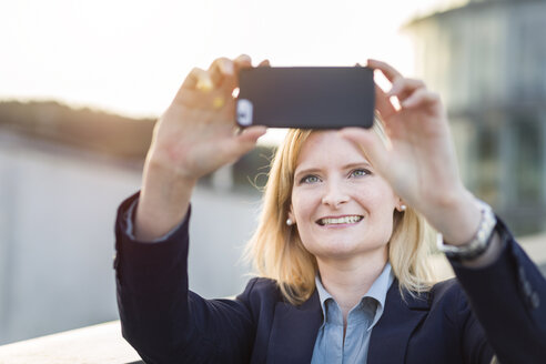 Portrait of smiling blond businesswoman taking selfie with smartphone - NAF000043
