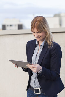 Smiling businesswoman looking at tablet - NAF000049