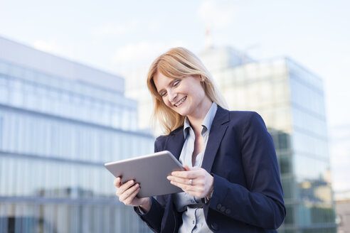 Content businesswoman looking at tablet - NAF000052