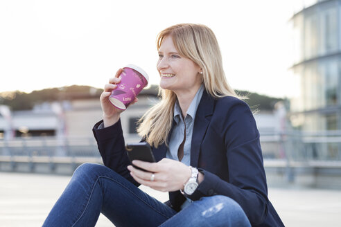 Smiling blond businesswoman with smartphone and coffee to go - NAF000055