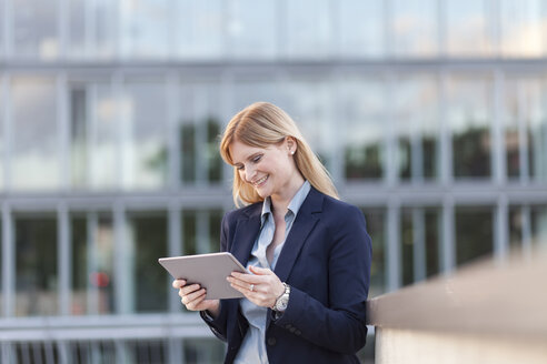 Smiling businesswoman looking at tablet - NAF000058